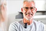 Mann in mittleren Jahren mit Mikrofon am Pulloverkragen