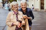 Zwei lachende Seniorinnen in einer Fußgängerzone