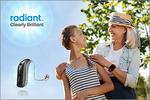Hörgerät von Sonic neben aktiver Seniorin mit Enkelin vor blauem Himmel