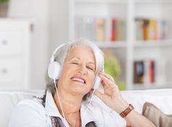 Seniorin hört mit Kopfhörern Musik.