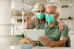 Mann und Frau mit Maske und Tablet